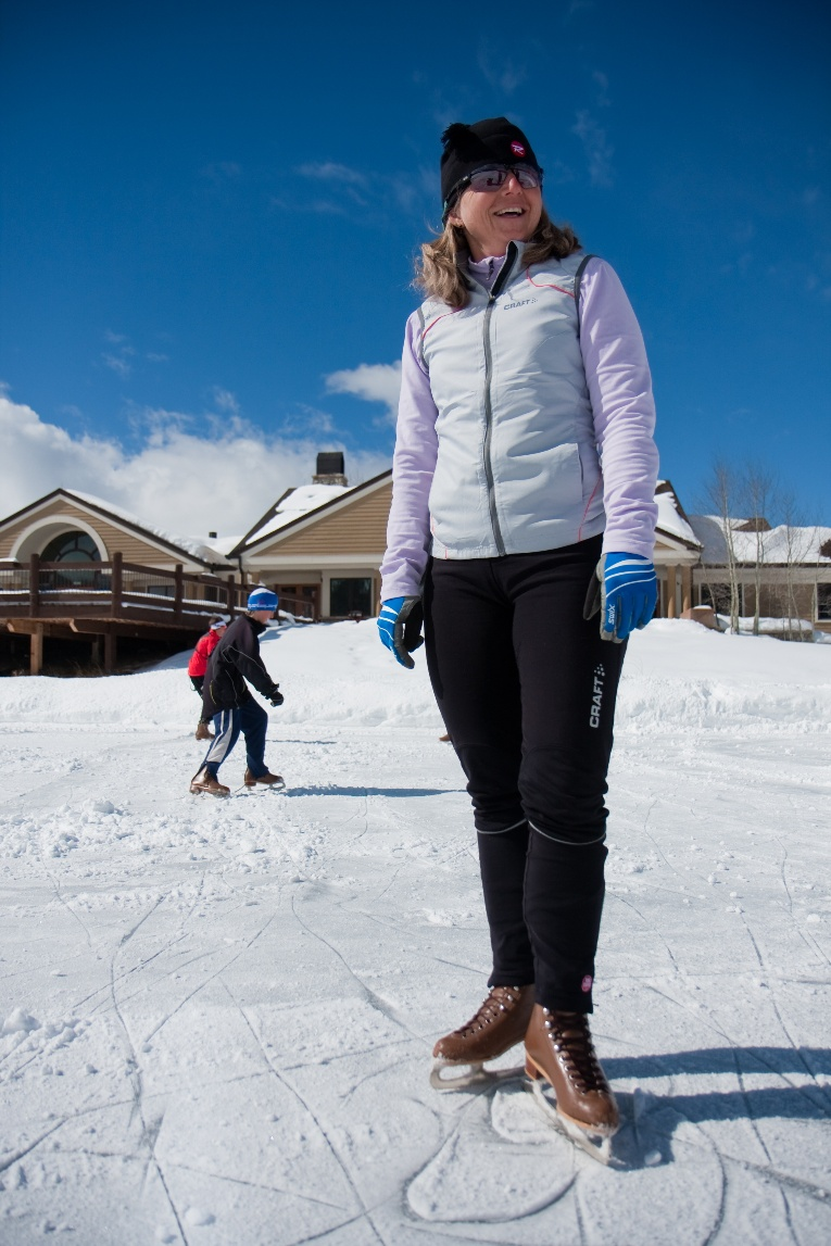 Woman standing on skating pond with two others in background