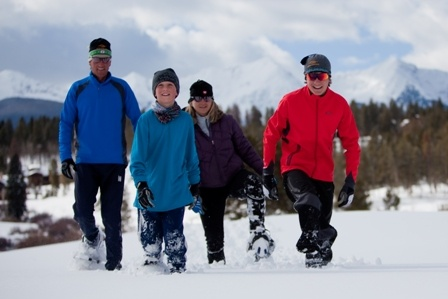 Smiling family outdoors on snowshoes with forest and mountans in the background