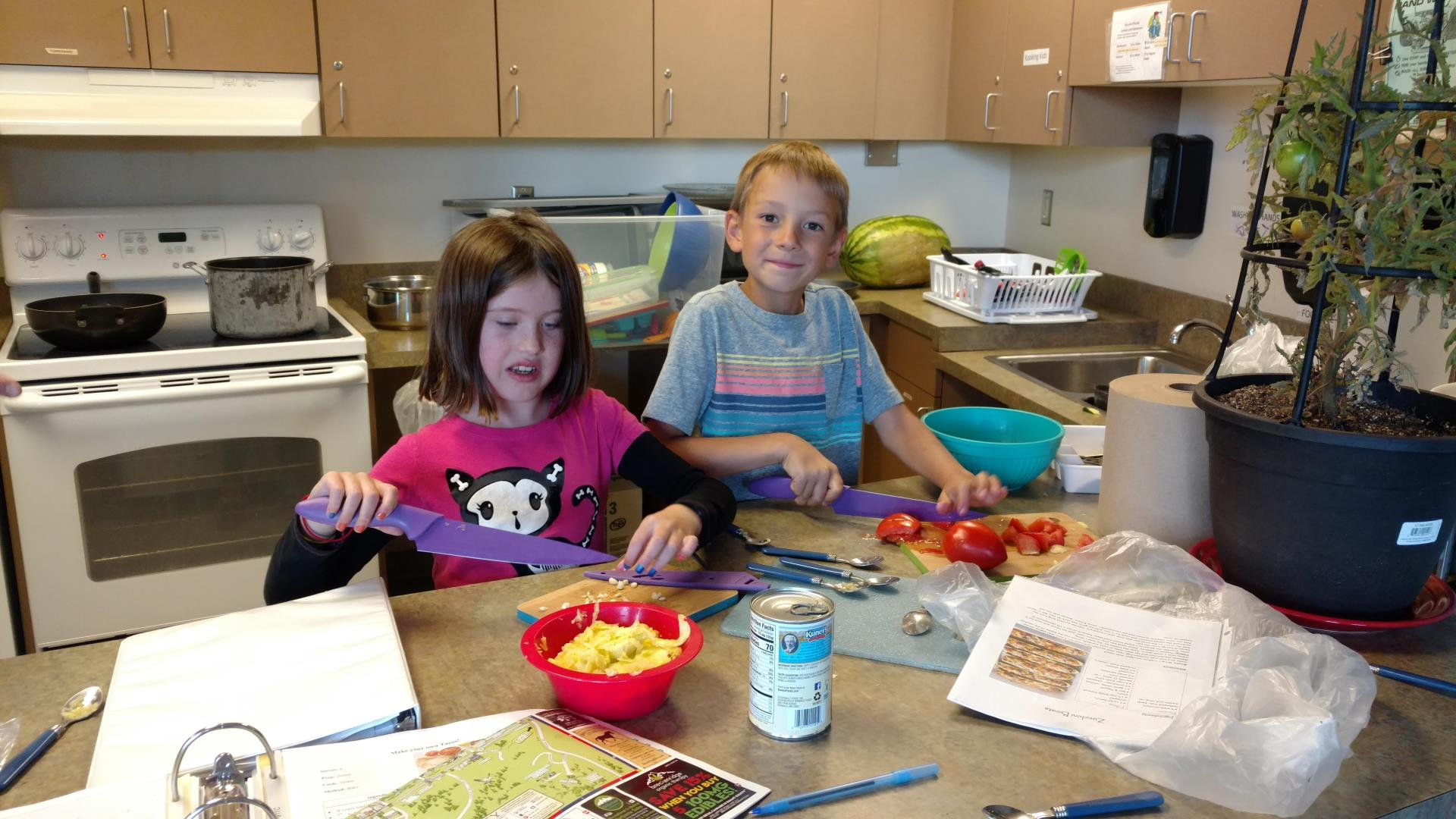 Boy and girl cutting up food in kitchen for cooking class