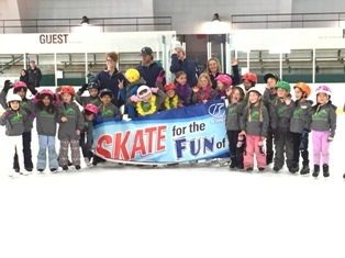 Large group of ice skating students and instructors with banner