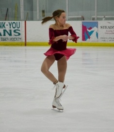 Girl in red skating dress performing jump in ice rink