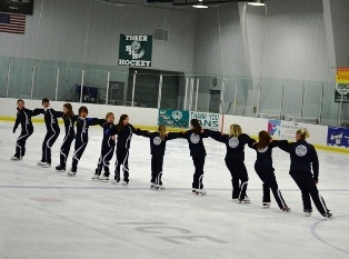 Ice skating instructors in blue uniforms performing figure skating spiral