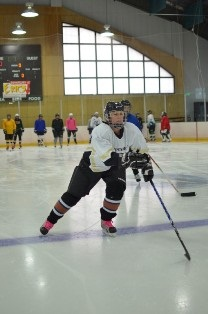 Female adult hockey player with stick on ice rink