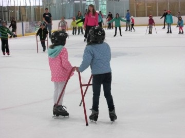 Two young girls ice skating with training aid in front of other skaters