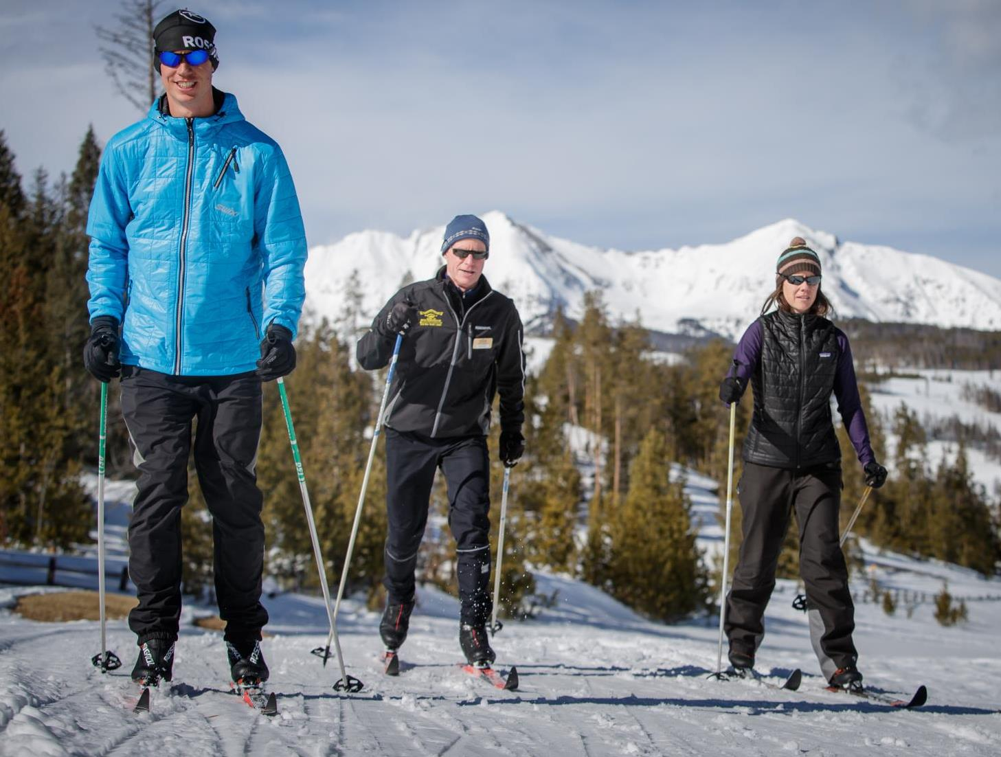 Two men and one woman Nordic skiing on a sunny day