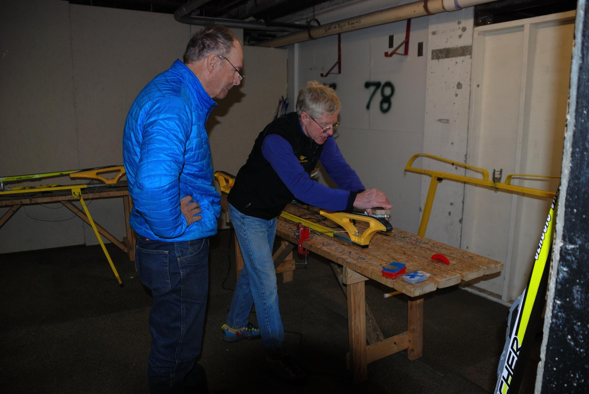 Two men in Gold Run Nordic Center tune shop working on skis