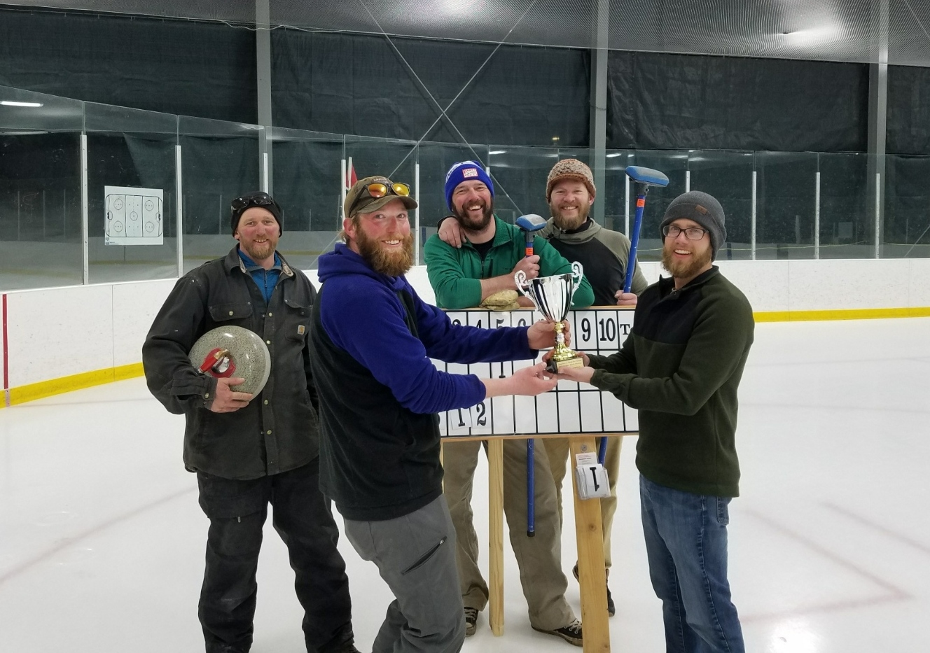 Five smiling males standing in ice rink with championship cup and curling equipment