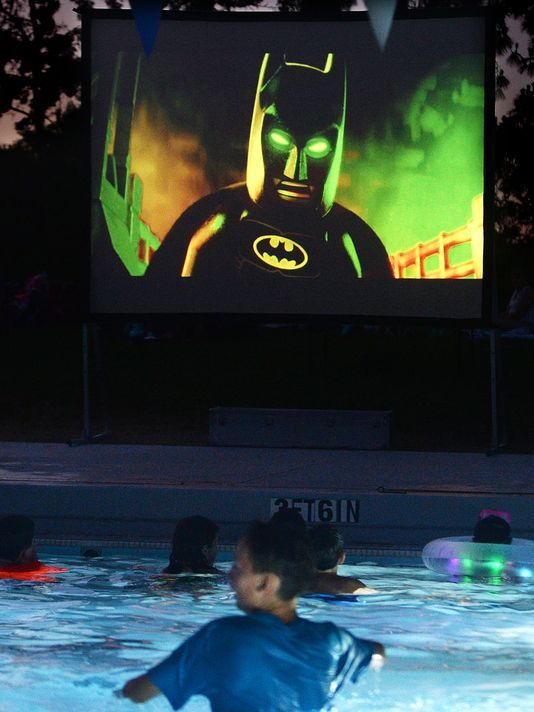 Boy in swimming pool watching Lego Batman movie