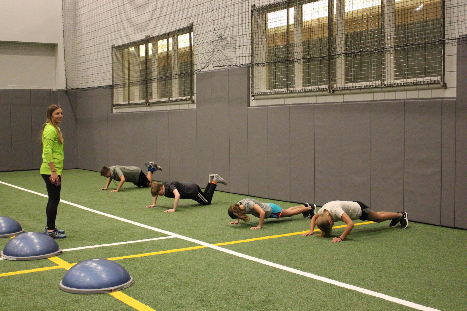 Teens doing pushups on turf field with trainer