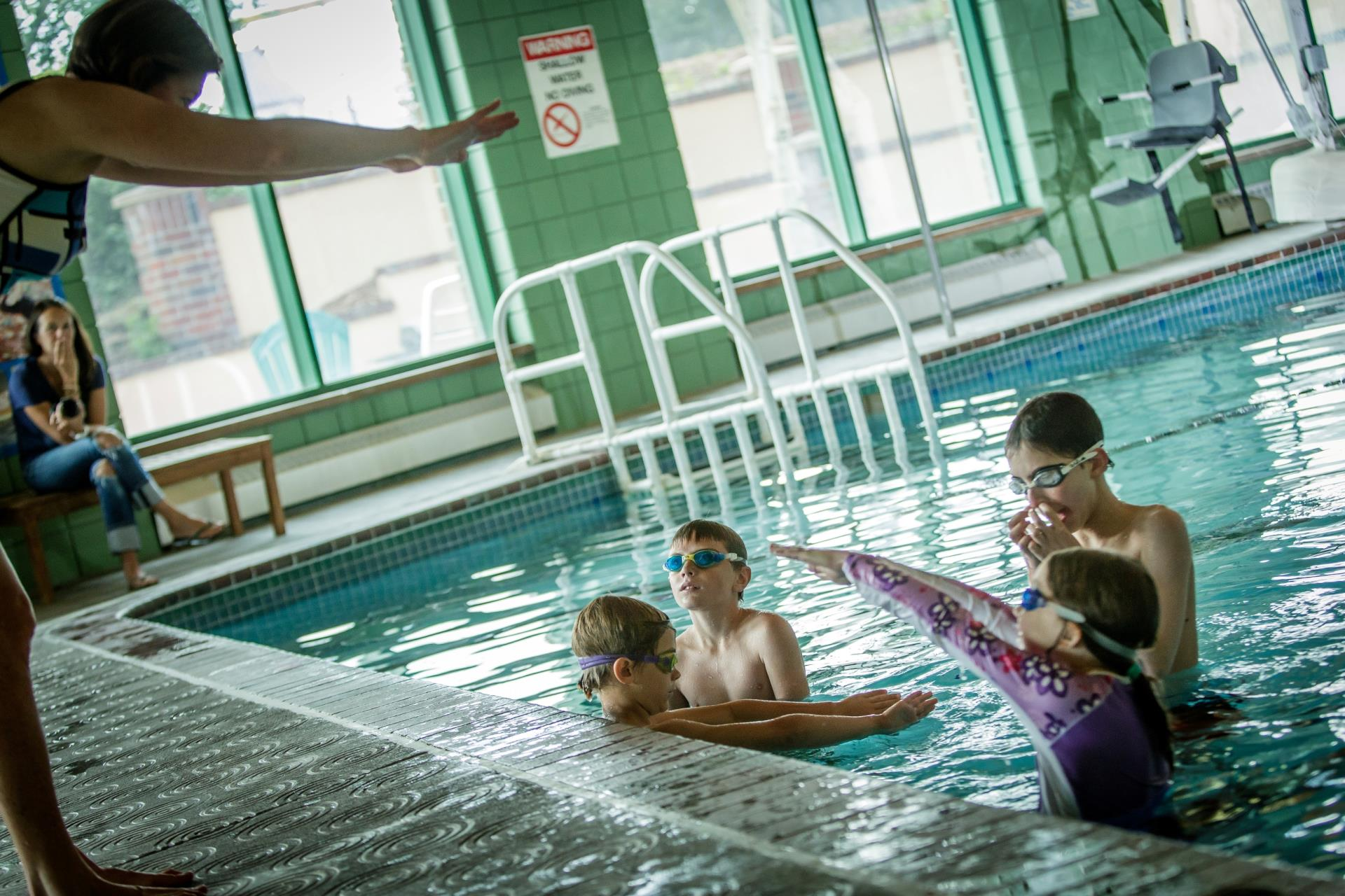 Group of 4 children in swim lesson in pool with instructor with diving arms on deck