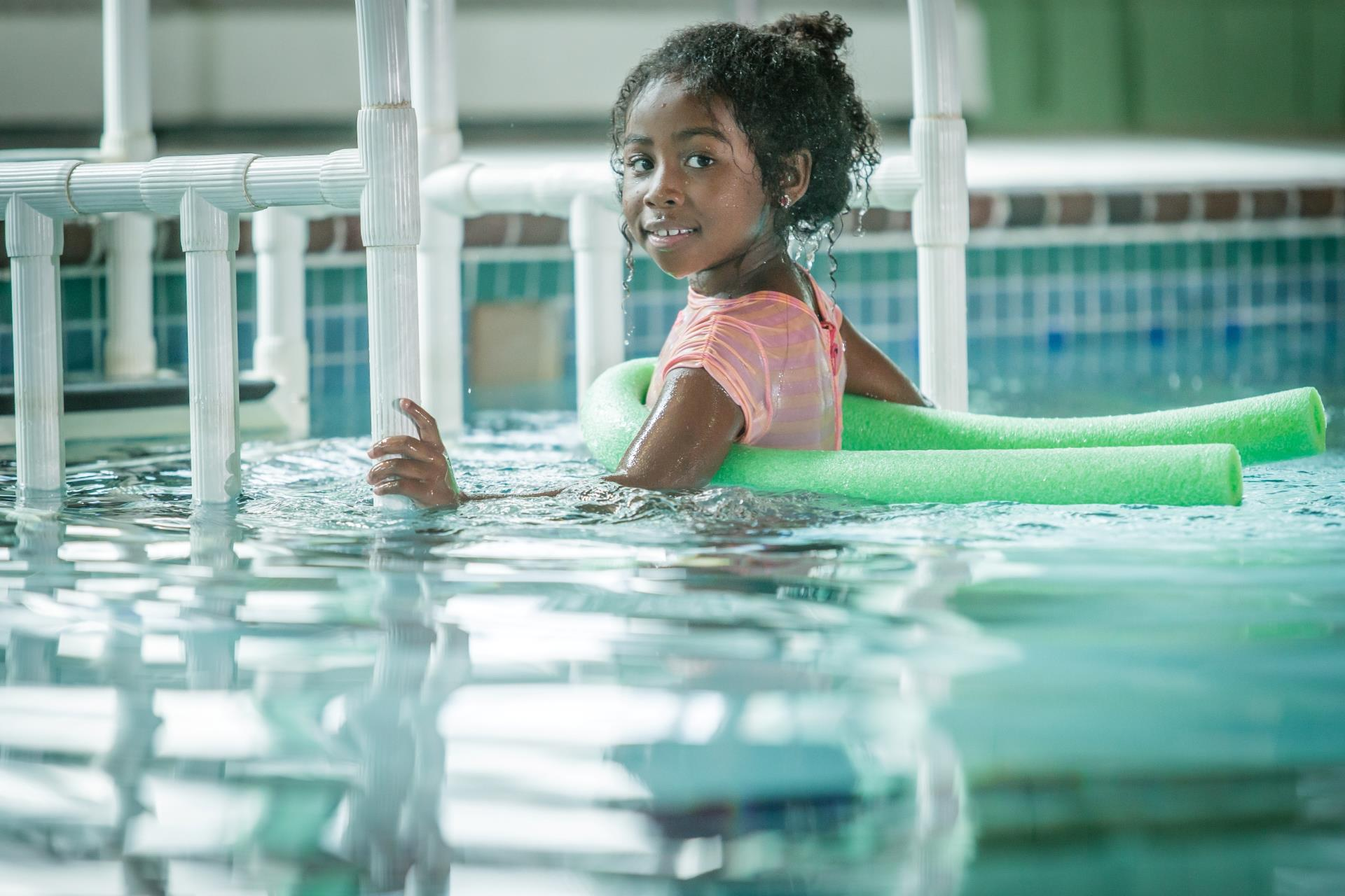 Young girl in swimming pool with float noodle