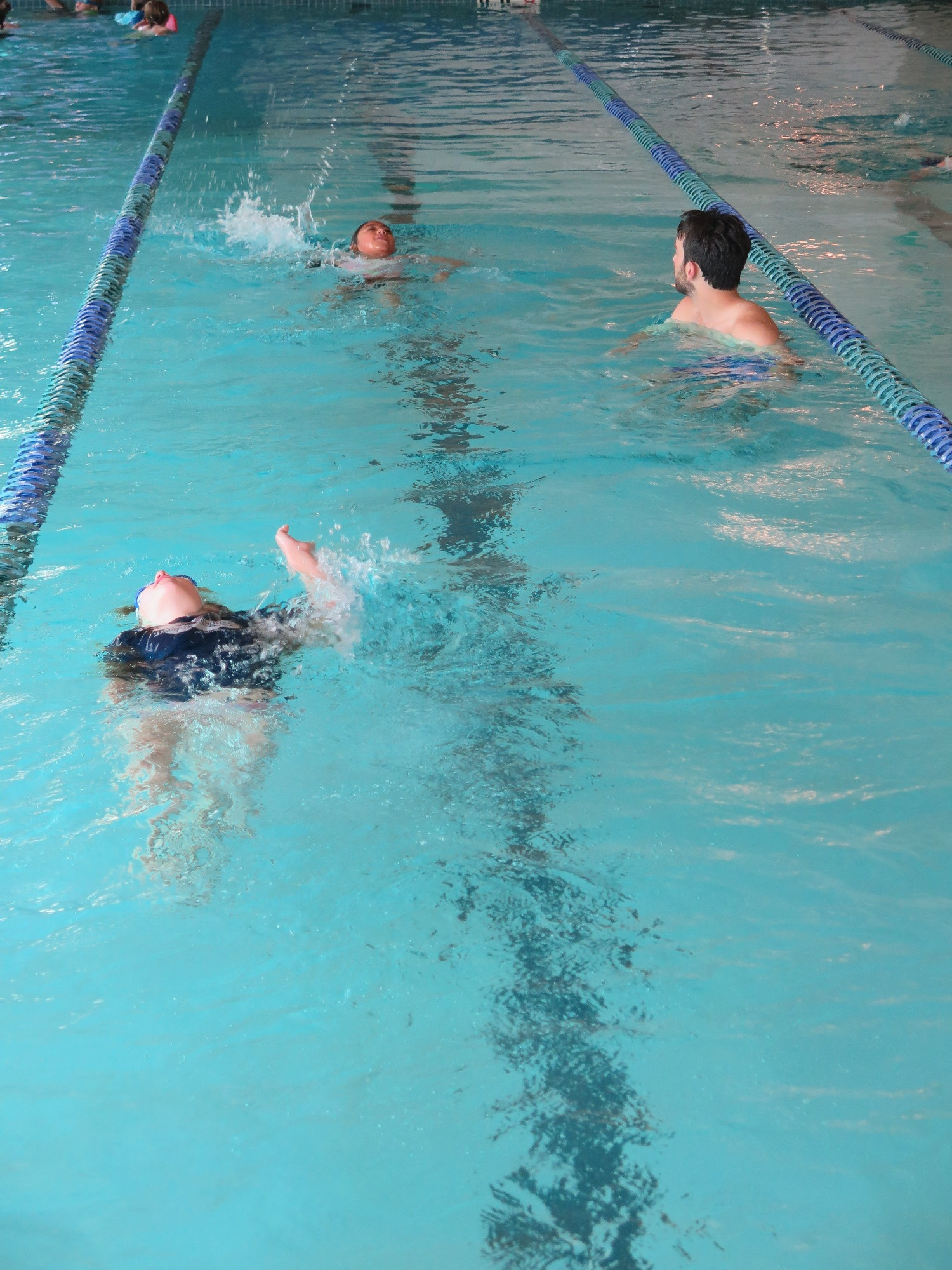 Two backstroking swimmers in pool lane with instructor