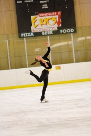 Female skater in black clothing performing spin on ice rink