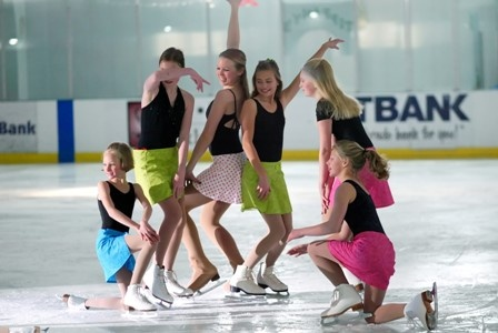 Group of six female ice skating performers posing on ice rink