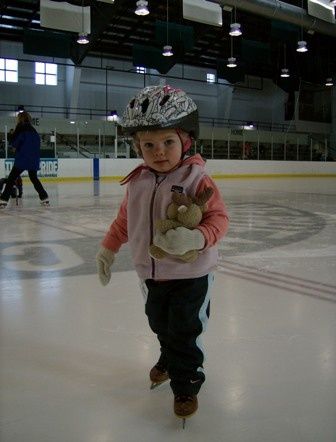 Young child ice skating with stuffed animal in arm