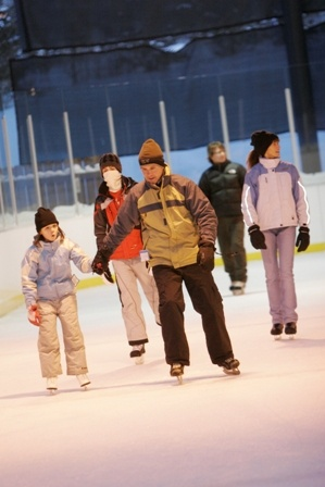 Group of five people ice skating in winter clothing