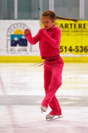 Girl ice skater in pink outfit performing spin on ice rink