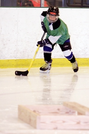 Youth hockey player stick handling on ice rink