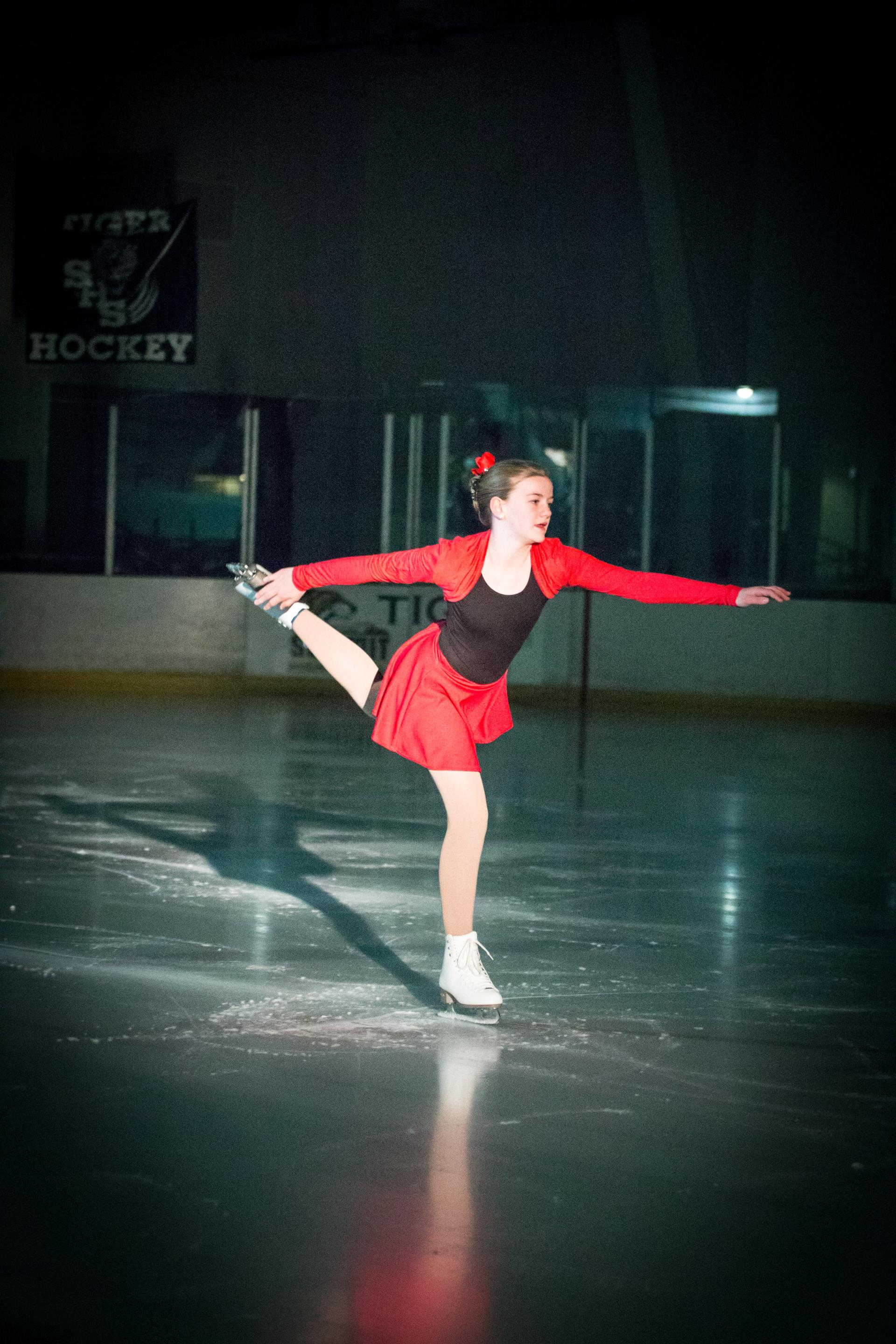 Girl in red and black dress skating on one leg in spotlight