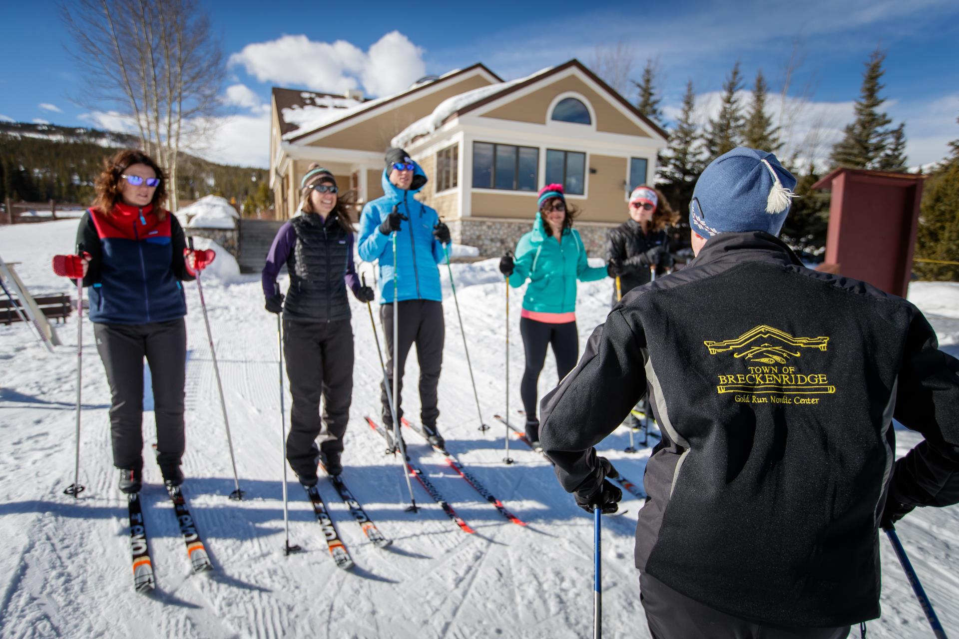 Cross-country skiing instructor giving lesson to 5 skiiers