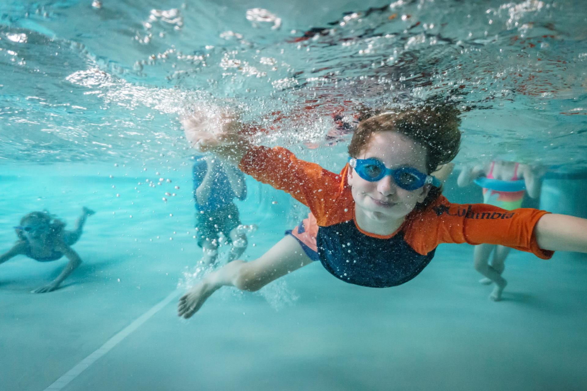Boy in blue and orange shirt and goggles underwater with other children