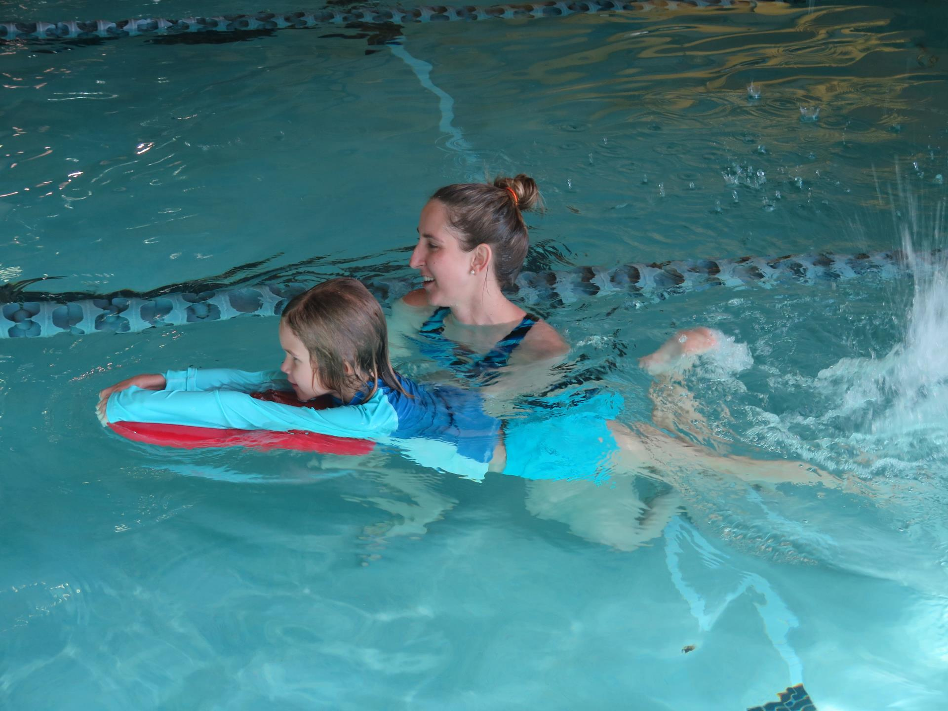Female swimming instructor with girl with kickboard in pool