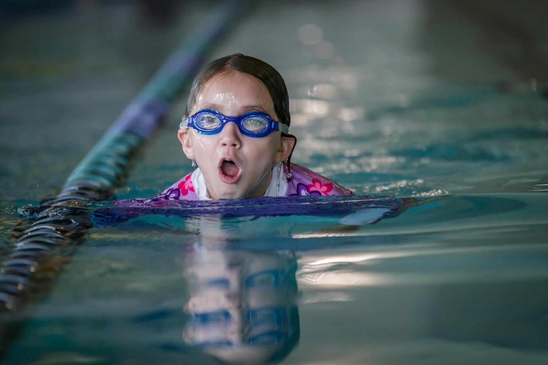 Child in goggles swimming in pool