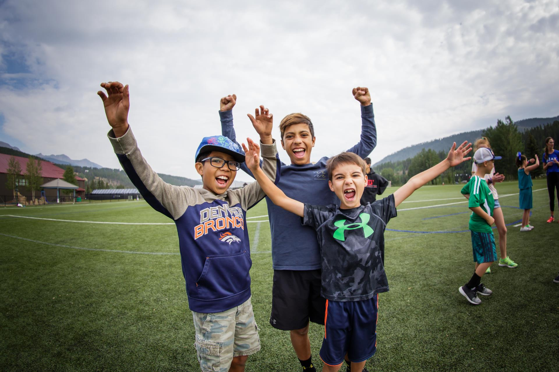 Three young boys outside on field with arms raised