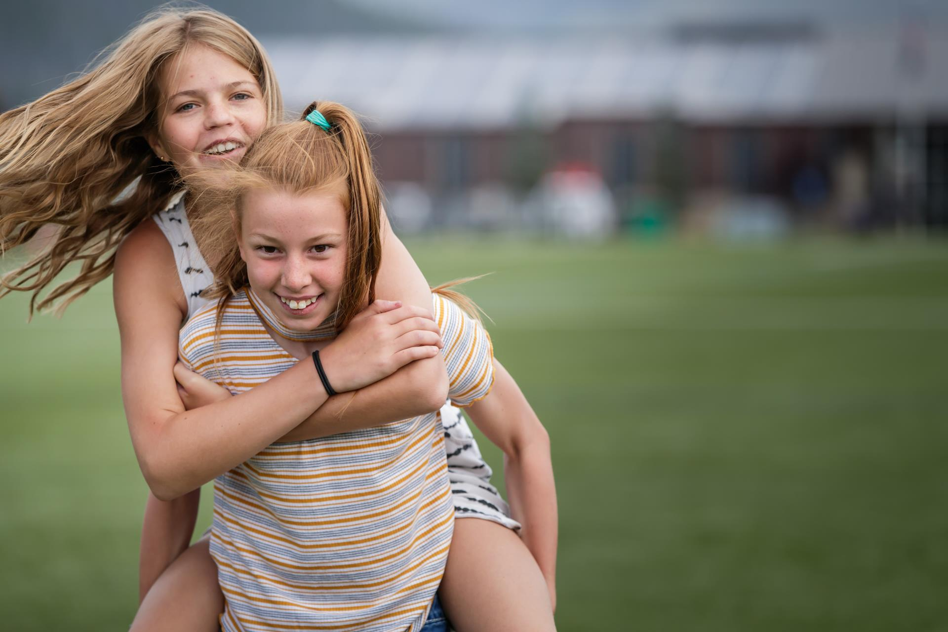 Girl giving piggyback ride to another girl outside on field