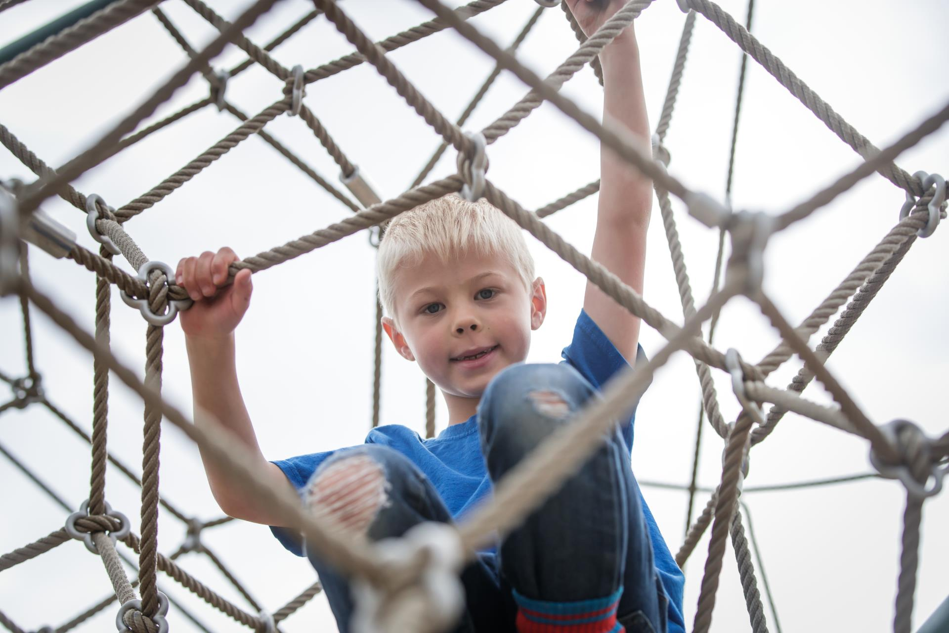 Boy on playground rope tower