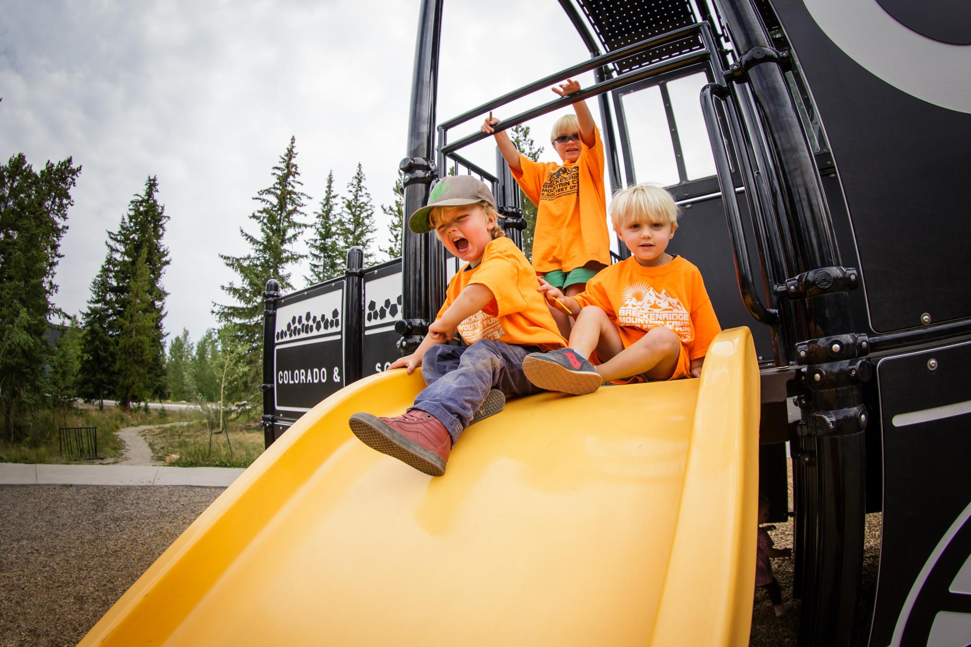 Three young boys at top of slide at the Railroad Playground