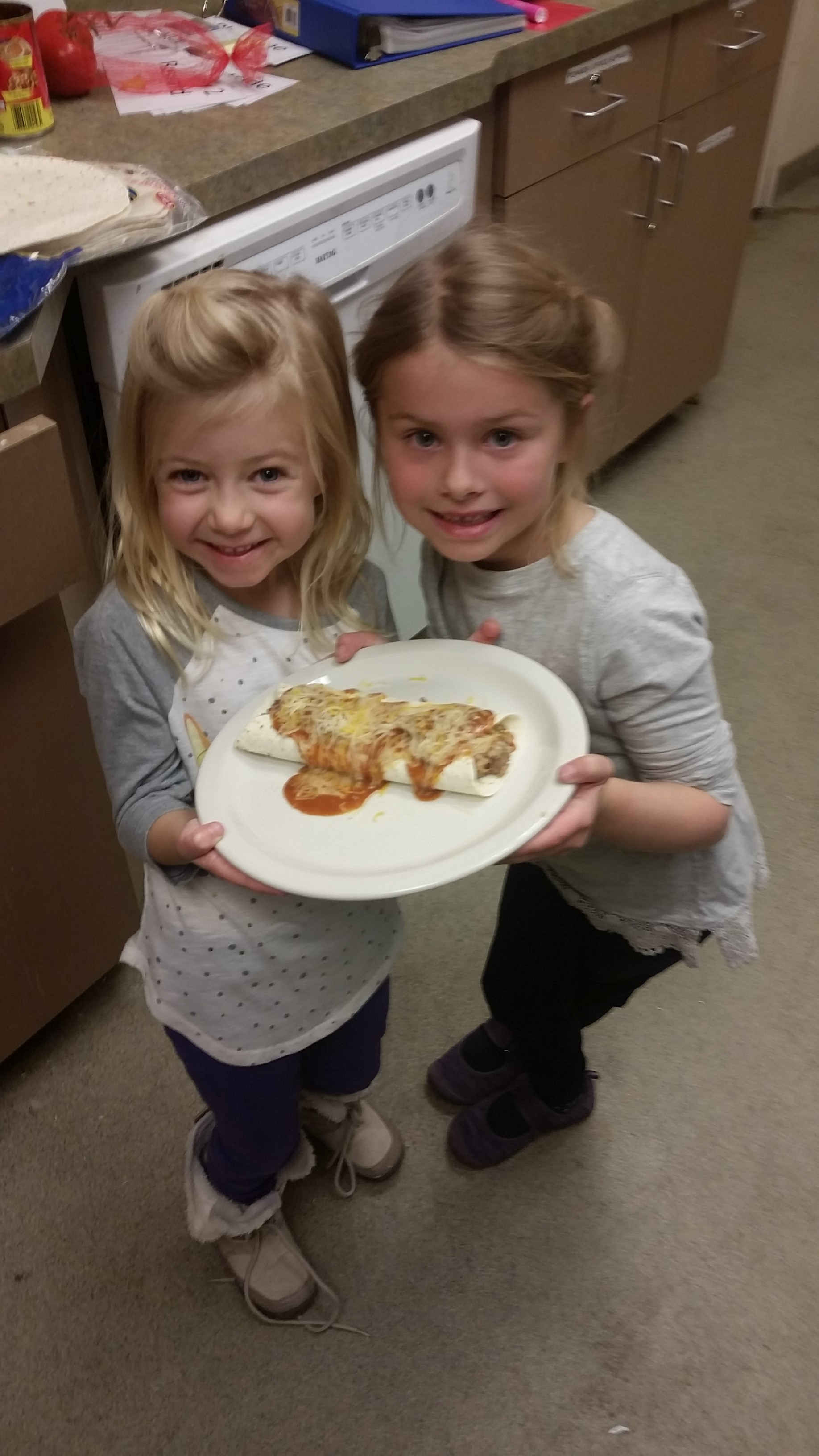 Two girls in cooking class holding plate of food