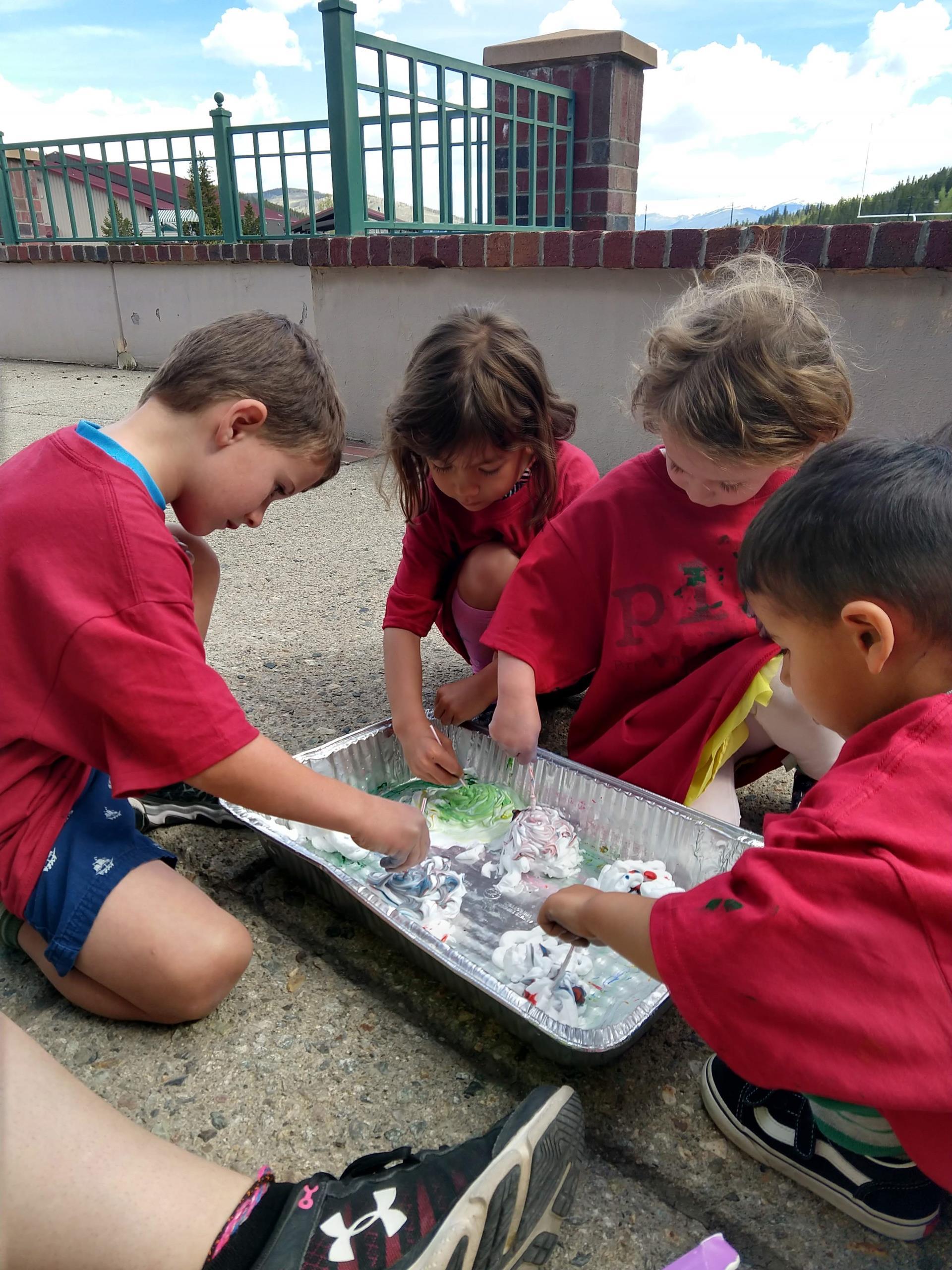 Four preschoolers working on craft