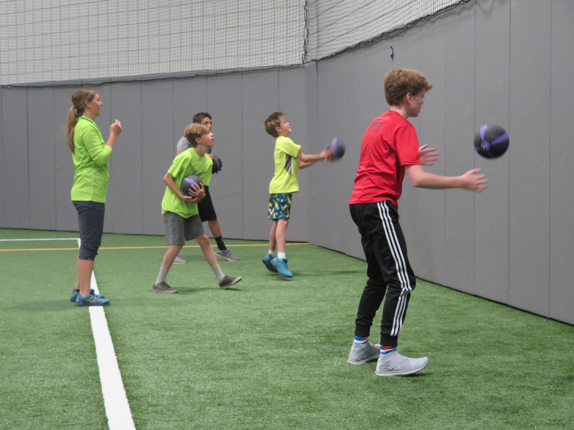 Teen boys and trainer exercising with medicine balls in turf gym
